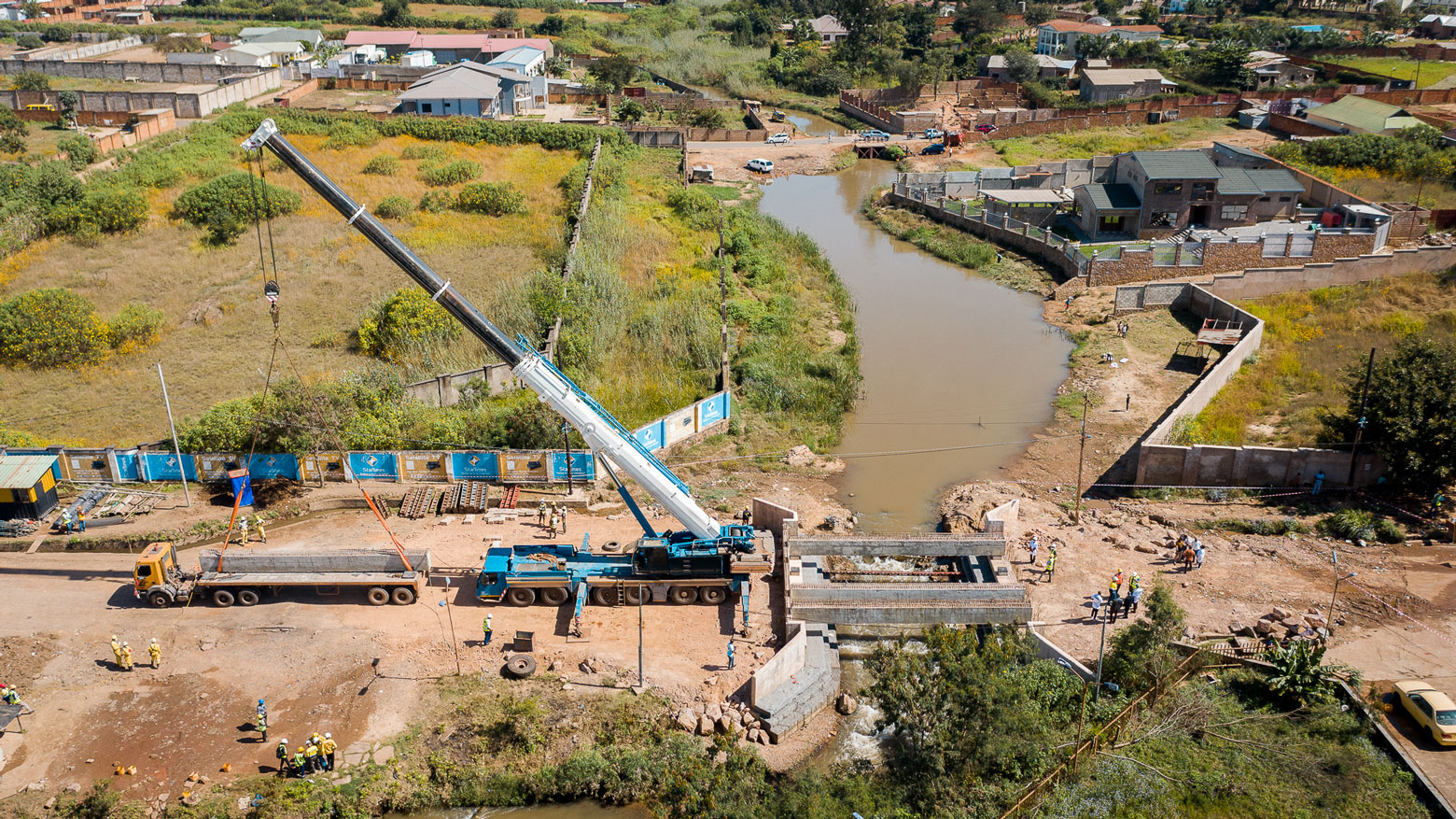 Pose d'une poutre lors de la construction d'un pont en RD Congo